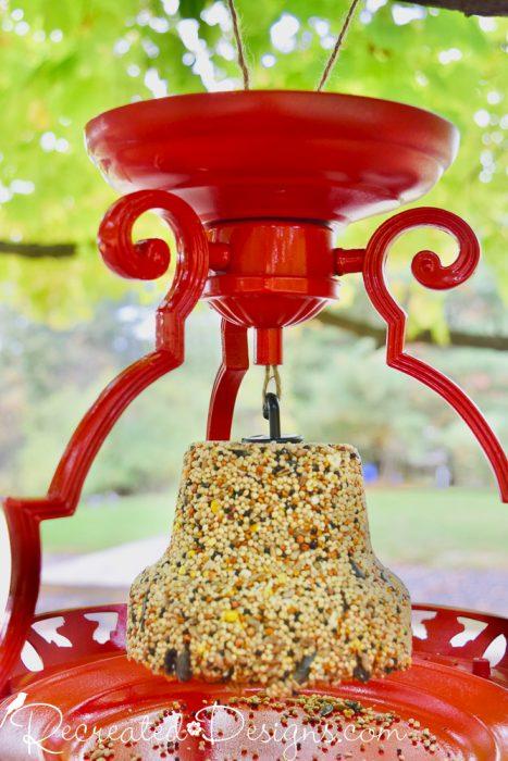 handing a bell of birdseed from a bird feeder