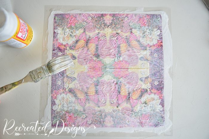covering a napkin with mod podge