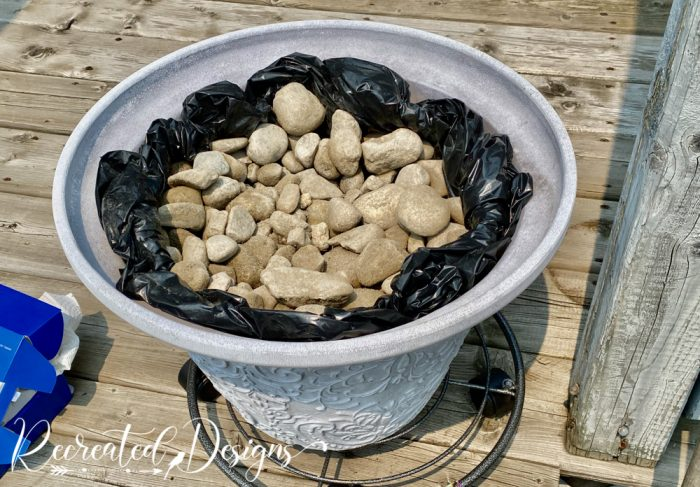 flower pot filled with a liner and rocks