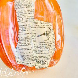 decoupaging book pages onto pumpkin